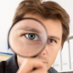 A businessman looking through a magnifying glass.