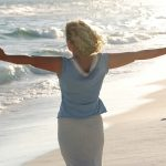 A woman at the beach with arms outstretched