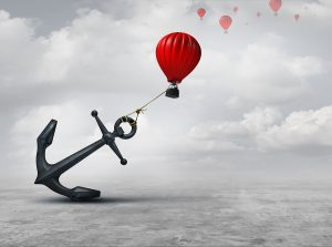 An anchor holding a red hot air balloon back.