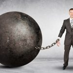 A businessman attached to a large ball and chain.
