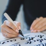 Calligrapher hands writes phrase on white paper. Inscribing ornamental decorated letters. Calligraphy, graphic design, lettering, handwriting, creation concept.