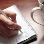 Womans hand with pen notebook and coffee