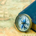 The compass beside a blue book with a cross on the cover. The compass and the book is on top of a navigational map