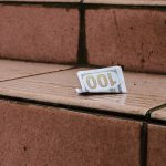 A folded $100 bill left behind on outdoor steps